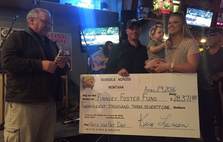 """At abenefit auction held at the Sting Sports Bar in Great Falls,Conrad High School principal Ken Larson, who spearheaded the """"wear a cap"""" fundraiser, presented a check for $28,371 to a speechless Foster family."""